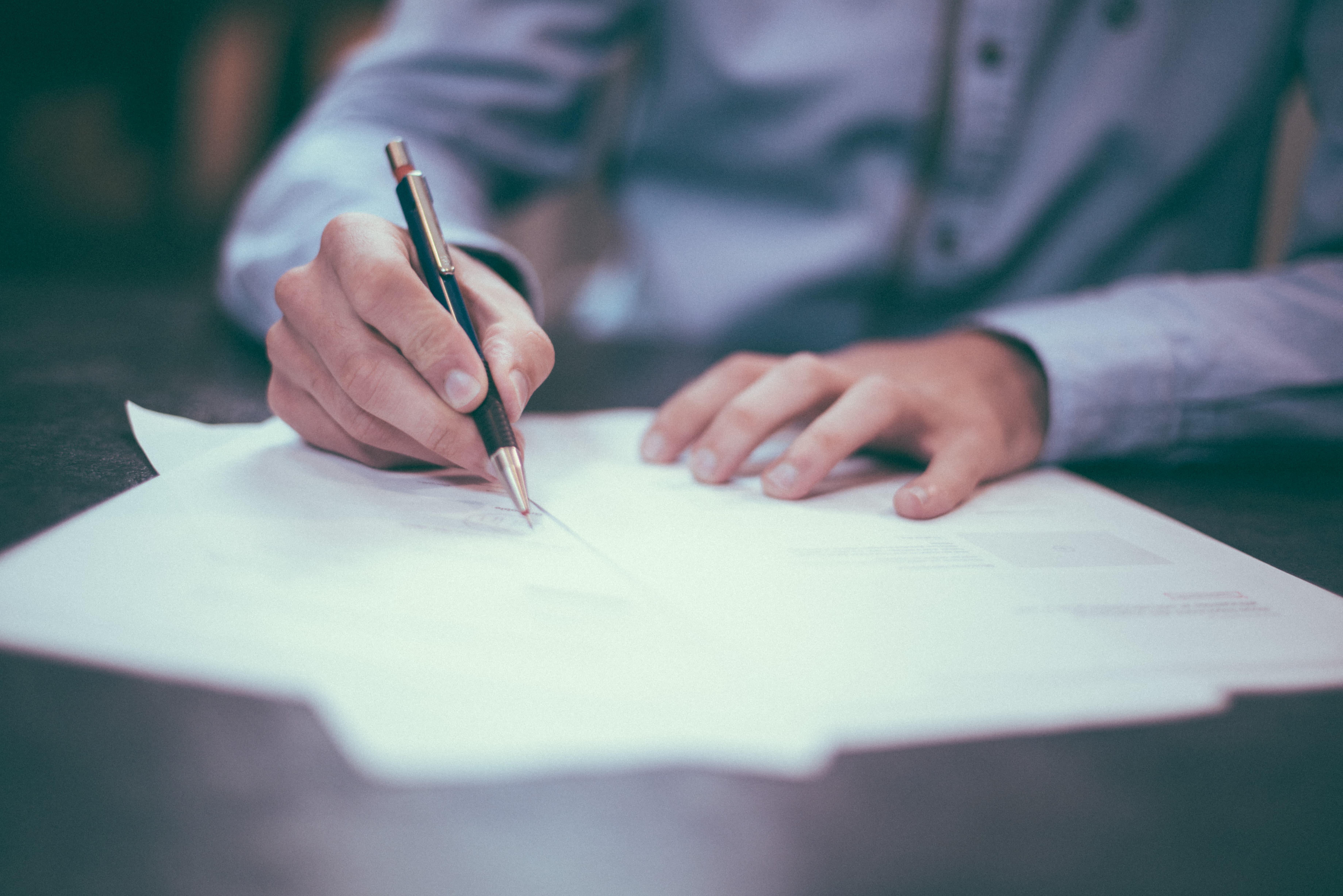 Pracownik podpisuje dokumenty - Pracownik wypełnia dokumenty